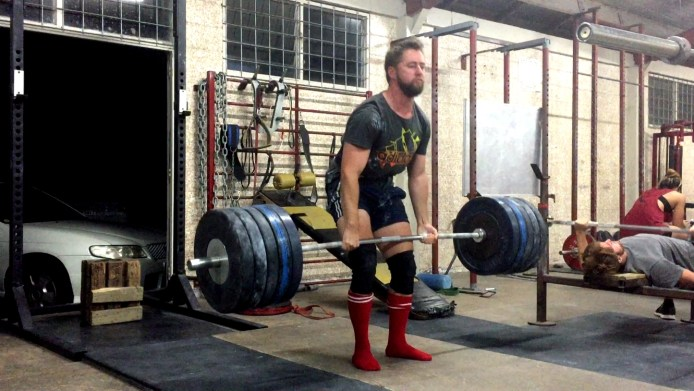 Deadlifting a 210kg barbell.