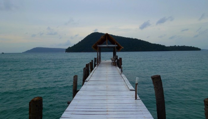 How to save $100k by age 25 cover image: a pier off the coast of Koh Rong island, Cambodia