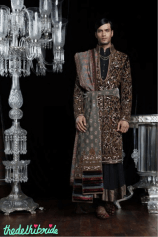 A chocolate velvet open neck sherwani with antique zardozi embroidery, worn with a long crinkled kurta embellished with antique borders and intricate zardozi buttons. Ensemble enhanced with a pre-pleated Jamewar shawl worn with jade green, zardozi embroidered kamarbandh with multi-coloured velvet borders and red velvet embroidered juttis.
