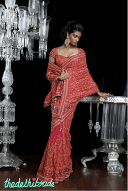 A beautiful sari in a splendid mix of Indian bridal colours, superimposed with aari work. Worn with a traditionally cut blouse