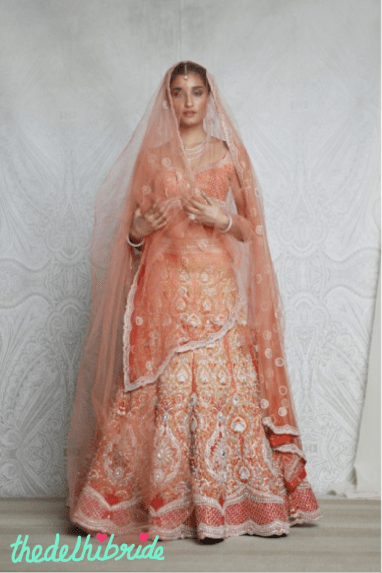 A bridal, kalidar lehenga, in different shades of orange, embellished beautifully with zardozi and Swarovski Elements. Worn with a tulle veil with ornate soldered elements.