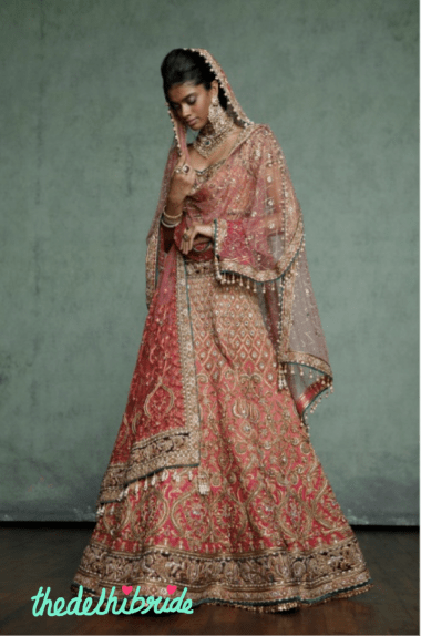 A rich, kalidar bridal lehenga, in different shades of orange & pink, with heavy zardozi embroidery on ornate motifs and contrasting embroidered borders. Worn with a traditionally cut blouse and pre-pleated drapes