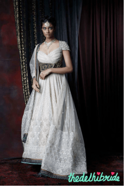 A zardozi embroidered sheer silk anarkali in elegant ivory with a contrasting black velvet border, lifted with jade lipping in raw silk. Bodice made with a champagne gold, fluted lurex jersey with kasab hand embroidery on the sleeves. Worn with a tulle dupatta and an antique zardozi embroidered belt enhanced with Swarovski Elements