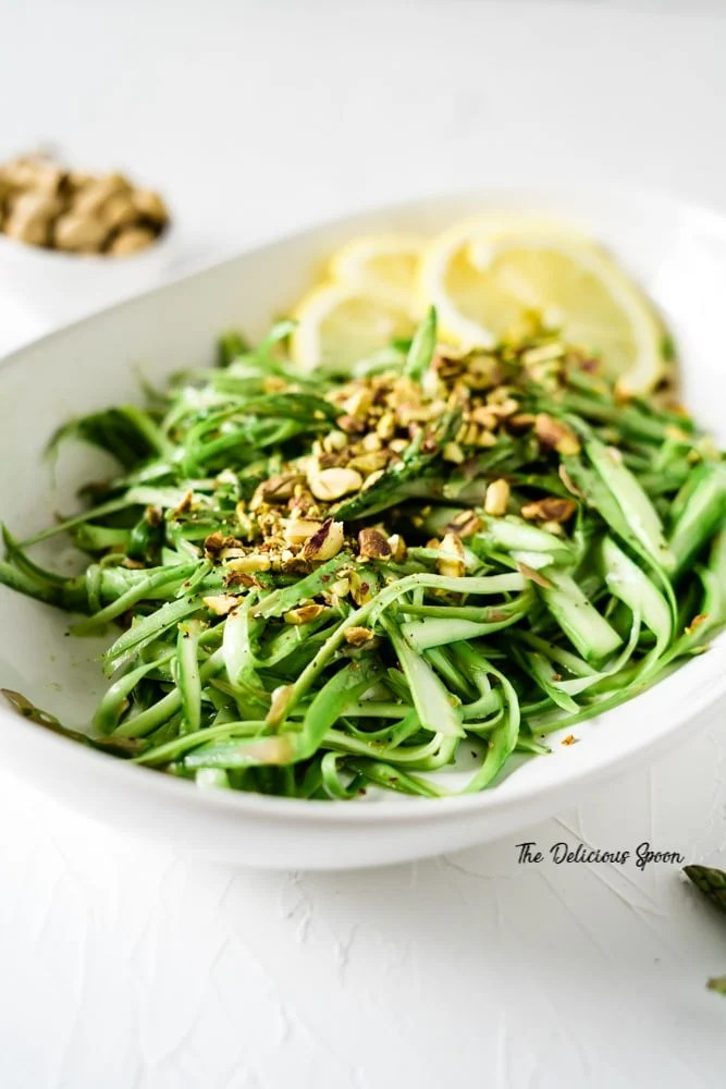 A bowl of asparagus salad decorated with lemons