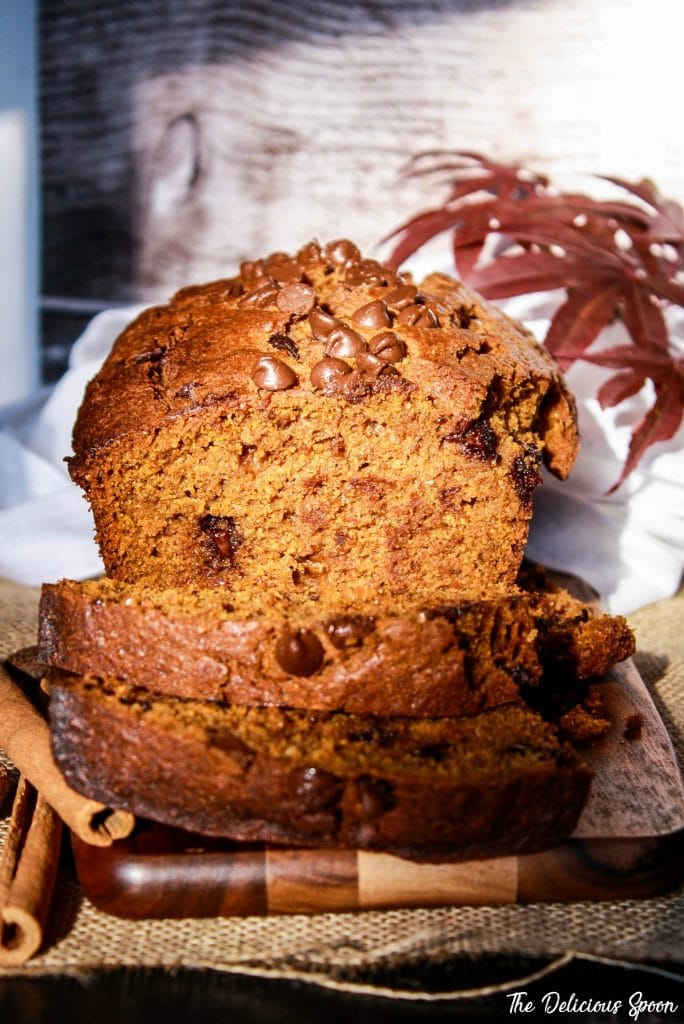 A head on shot of a loaf of Chocolate Chip Pumpkin bread with slices delicately falling in the front exposing the chocolate chips dotted inside.