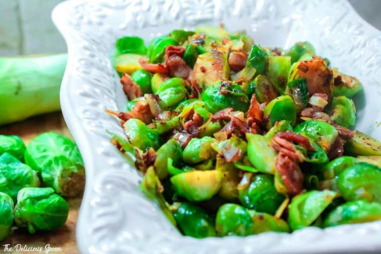 Pan roasted brussel sprouts and leeks tossed with crispy bacon inside a decorative white serving dish.
