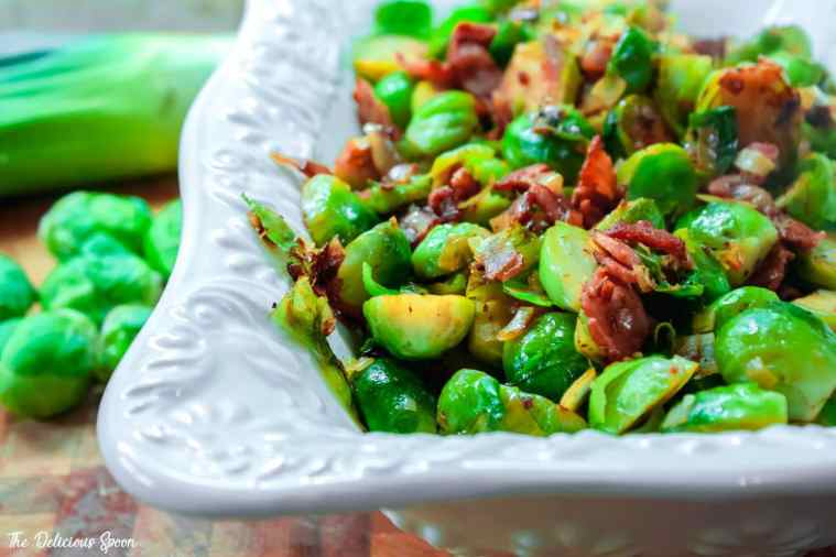 A decorative white serving dish filled with pan roasted brussel sprouts, leeks and bacon.