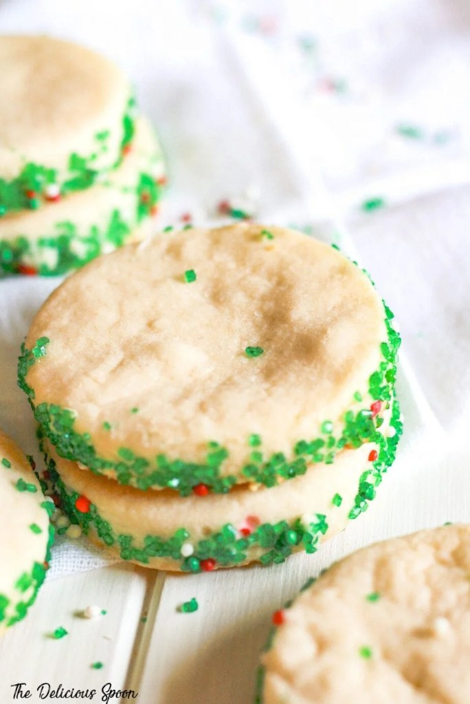 A close up of shortbread cookies rimmed with green sugar crystals