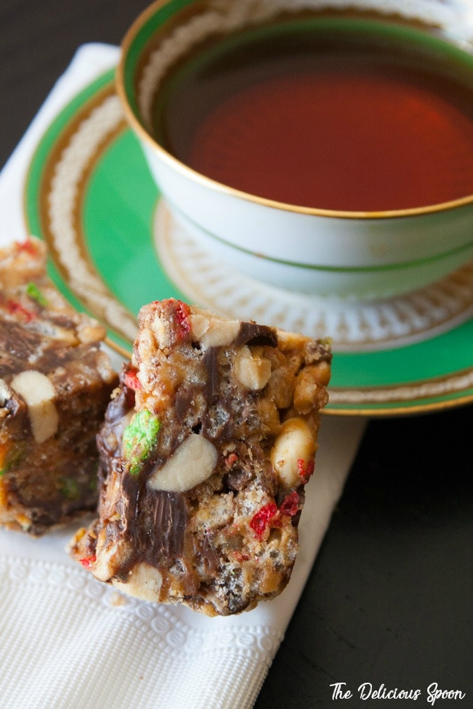 Two Chocolate Peanut Butter Bars laid out on top of a white napkin beside an old fashioned green and gold teacup