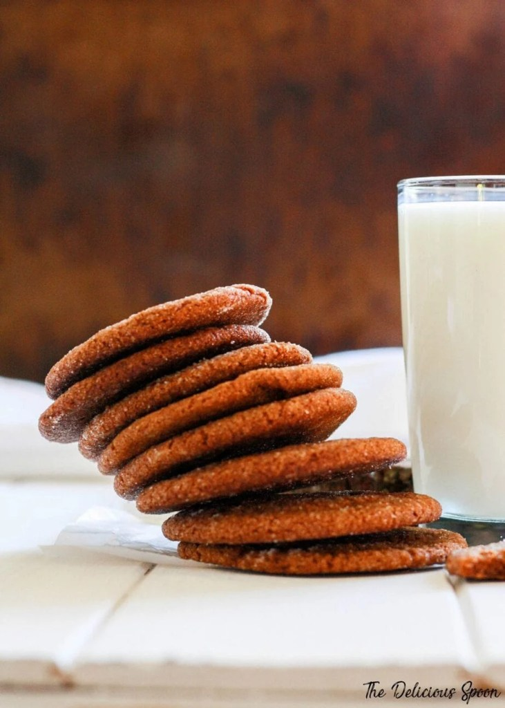 A tall stack of ginger snap cookies tumbling over beside a tall glass of milk