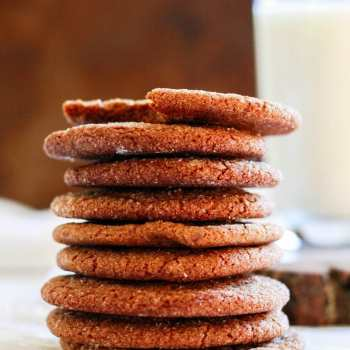A tall stack of ginger snap cookies with a glass of milk in the background