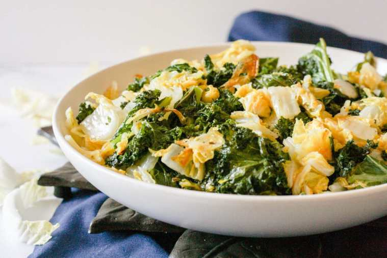 Close up photo of roasted kale and napa cabbage in a white bowl with a blue napkin