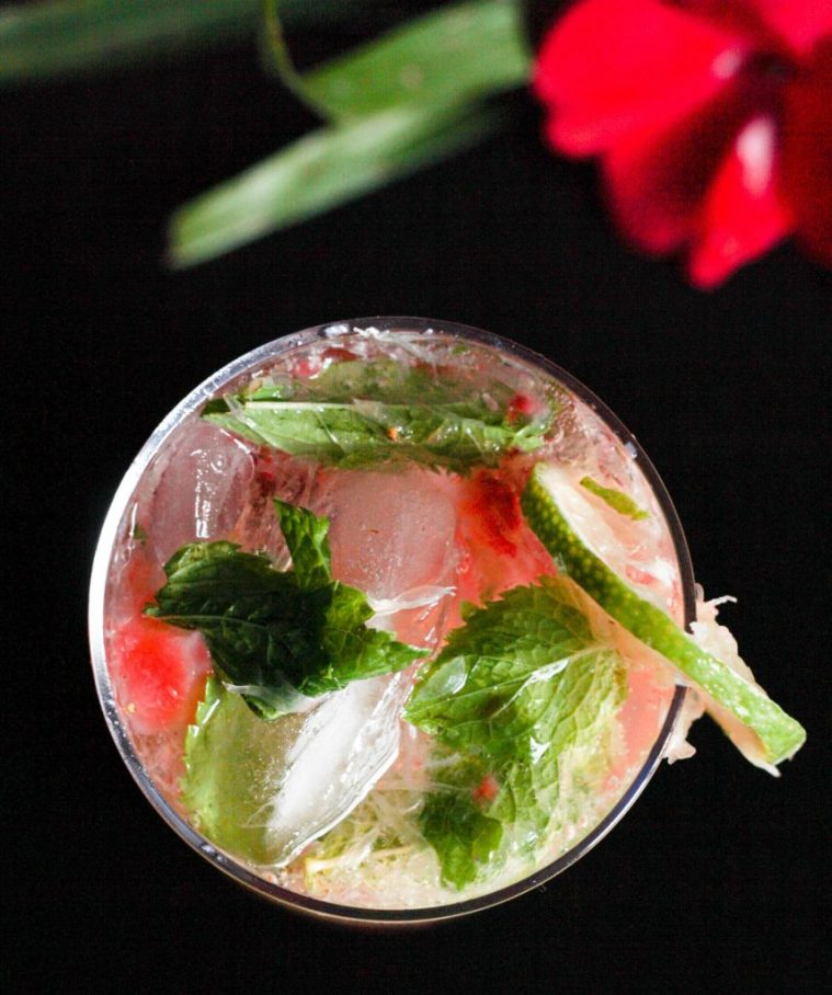 An overhead shoot of a freshly made strawberry mojito with some exotic red flowers and greenery.
