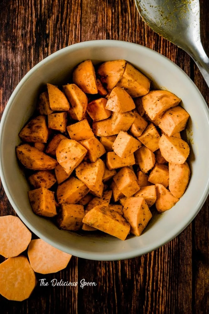 Bowl of seasoned sweet potatoes before they are baked