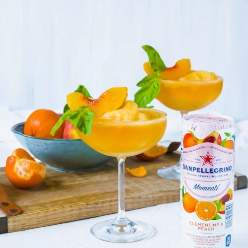 Two Bellini Mocktails in tall stemmed glasses topped with a peach wedge and basil #shop #cbias