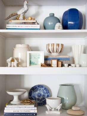 Designer Emily Henderson used stacked books as platforms to give this gorgeous bookcase vignette some height. This is such a beautiful collection of items - love the use of colour! | via http://stylebyemilyhenderson.com/blog/announcing-styling-how-tos/