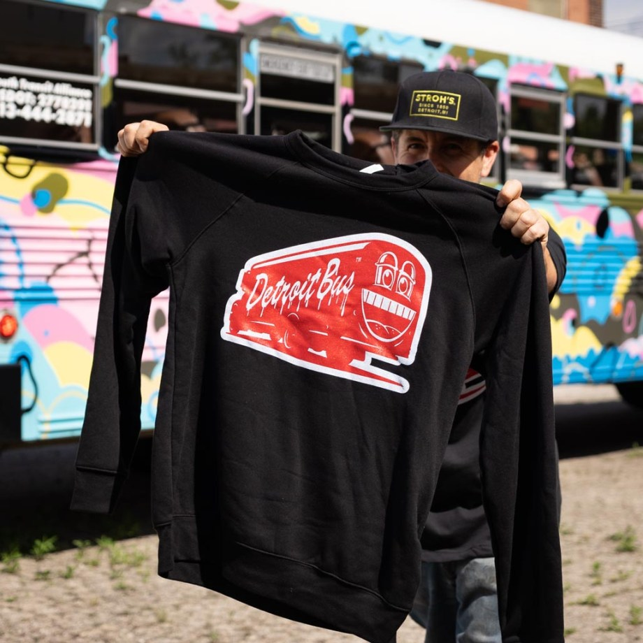 Person holding art bus smile sweatshirt up for camera in front of another art bus