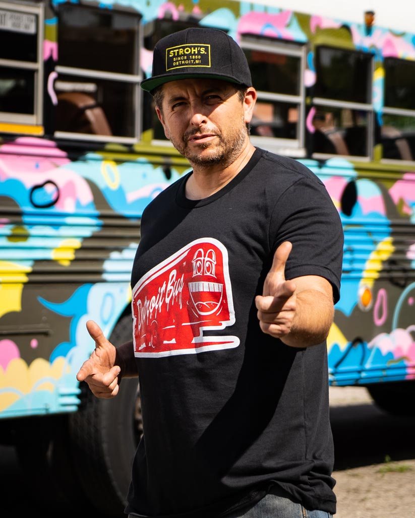 person wearing art bus smile t-shirt finger pointing at camera with both hands