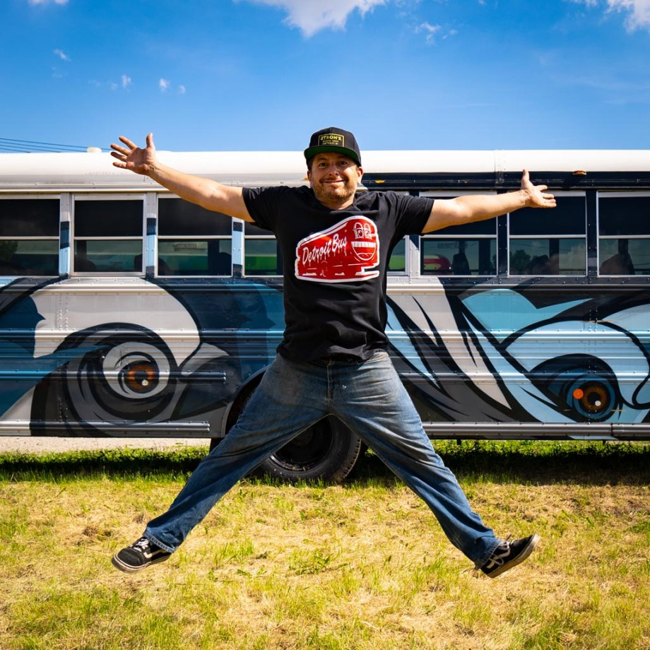 person wearing art bus smile shirt jumping in front of another art bus