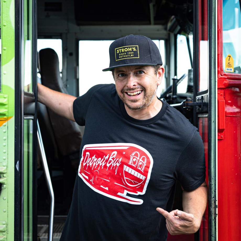 person wearing art bus smile t-srhit staging int doorway of another art bus while pointing to the shirt's graphics