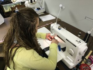 Kelly Bolyard sewing a bag. (PHOTO: Megan Combs/The Devil Strip)