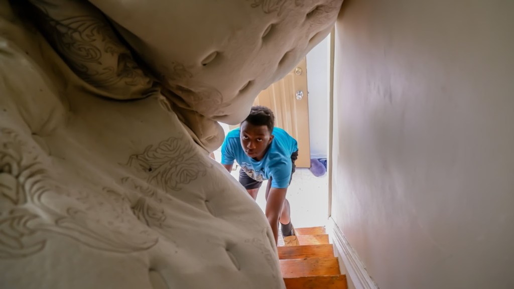 Amber Moreland's teenage son helps move a mattress down a flight of stairs.