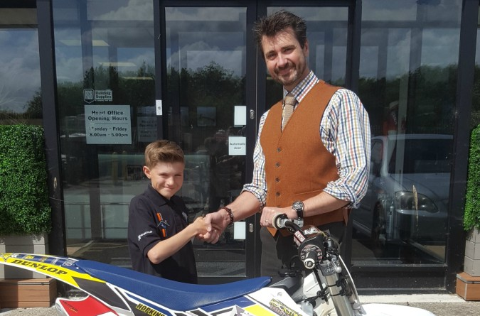 George Hopkins and Paul Turner with George's bike and the trophy he received for being crowned the 2016 South West 65cc Motocross Champion.