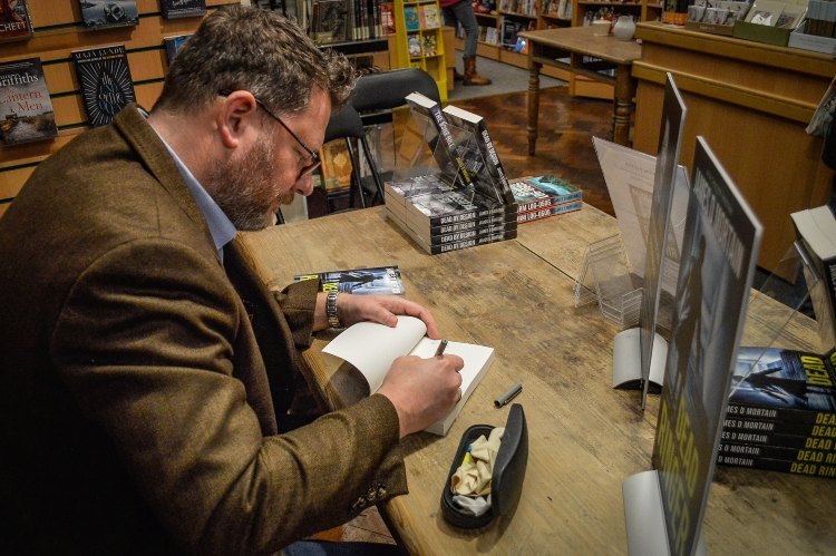 a man is sitting a table signing books