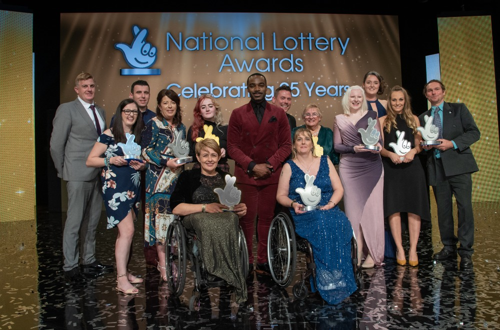 a group of people in front of the National Lottery logo
