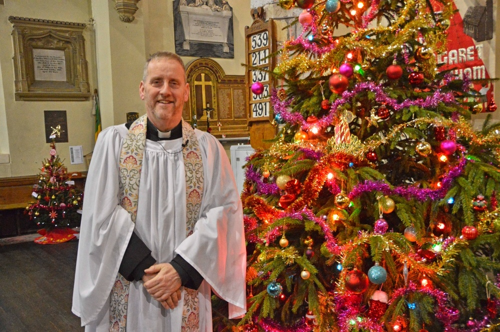 a vicar in from of a Christmas tree in a church