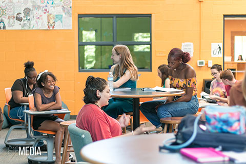 Picture of students talking with each other in a classroom