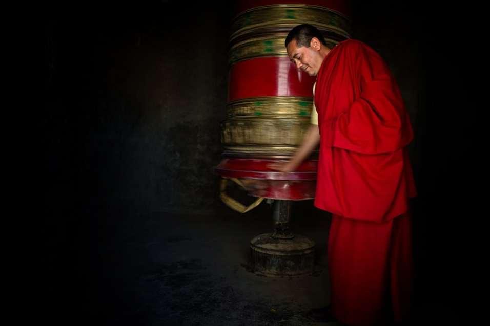 Buddhist monk in Ladakh spends a large prayer wheel.