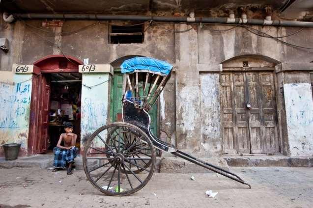 Parked outside a residence, this rickshaw awaits its puller. Kolkata, India