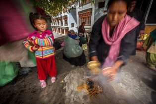A Ladakhi woman ceremonially cleans instruments of worship as her daughter watches on.