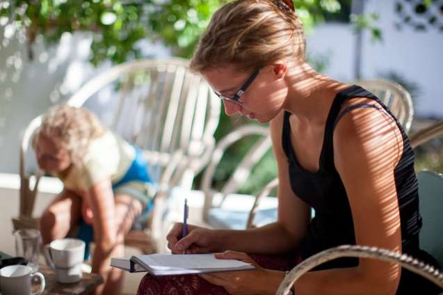 A volunteer writes each bird's data like; wing length, weight and age in a note book for future study.