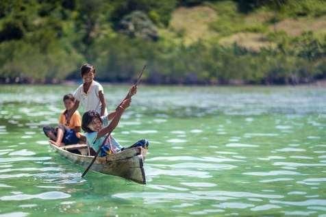 Bajau Laut girl punting her boat, Sabah