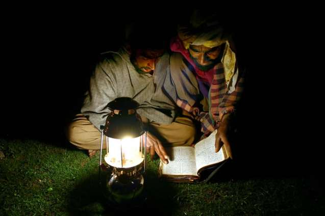 Two Gujjars reading a book by gas light.