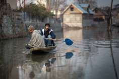 Two men paddle their shikara in Rainawari, Srinagar.