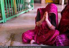 A woman prays as she sways to the chanting and music in the Radha Gopinath Temple.