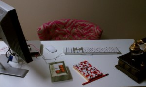 Glossy white desktop with pink zebra print office chair adds to the glamour