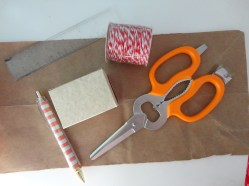 Now we're ready for wrapping! Cut the side of a brown paper grocery bag from Trader Joes, tape, and red & white bakery string from Target ($1)