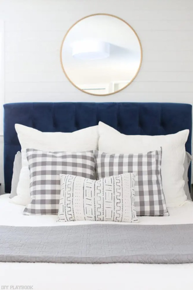 bedroom-navyheadboard-roundmirror-pillows