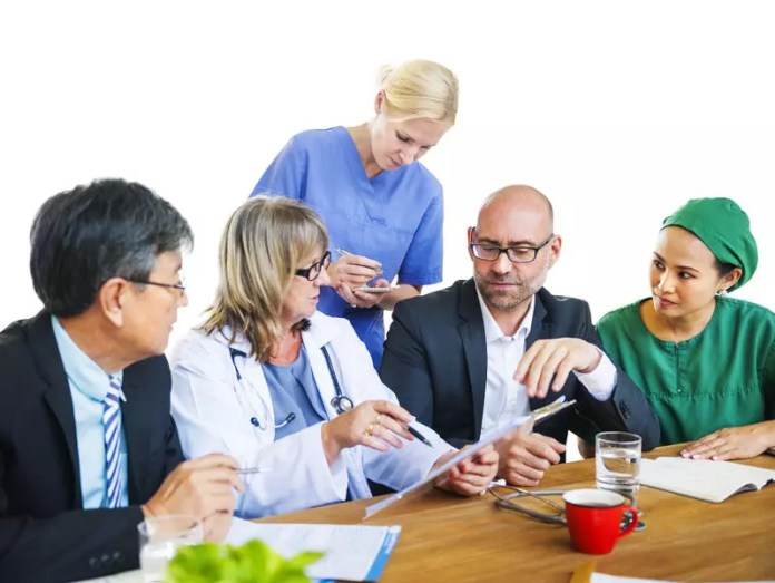 Doctors and managers at table discussion 799 x 600 px
