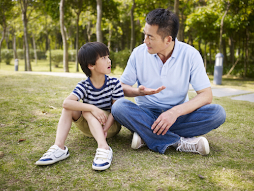Asian father and son talking