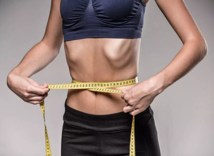 Young skinny woman is measuring her waist during diet.
