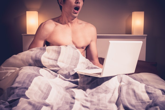 Young man is sitting in bed and watching pornography on laptop 1732 x 1155