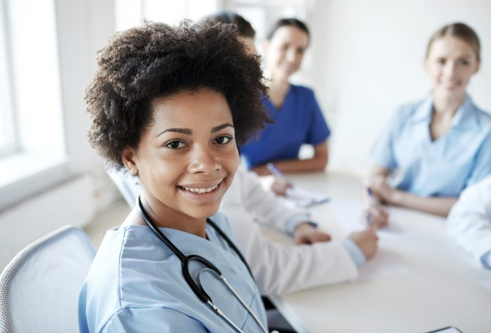 happy african american female doctor or nurse over group of medics meeting at hospital 2048 x 1389