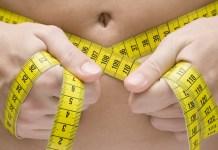 Woman measuring her waist. 2000 x 1333