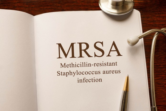Page with MRSA (Methicillin-resistant Staphylococcus aureus infection) on the table with stethoscope, medical concept 1500 x 1006