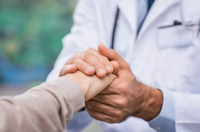 Male doctor holding female patient's hands 2125 x 1411